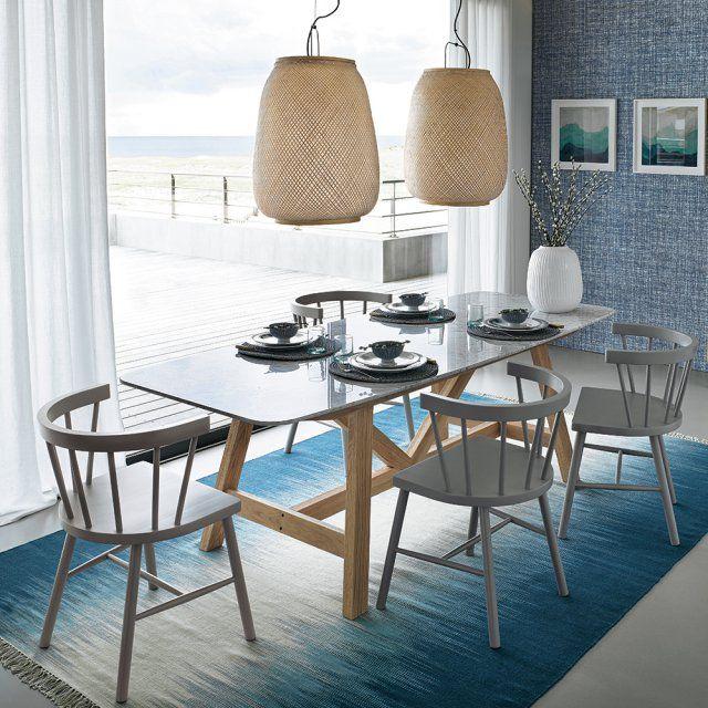 Une salle à manger entre terre et mer, AM.PM. Dans cette salle à manger, le tapis n'est pas sans rappeler les couleurs de la plage avec le sable et l'eau de mer. Les chaises couleur taupe s'installent autour d'un belle table au piètement de bois, et deux belle suspensions tressées surplombent la scène.