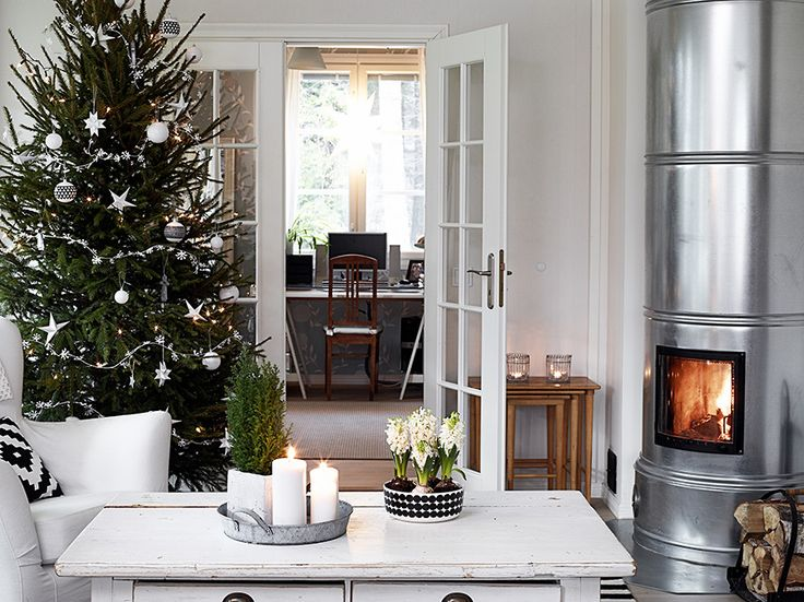 Scandinavian living room, with a silver fireplace, a Christmas tree and everything else is white.