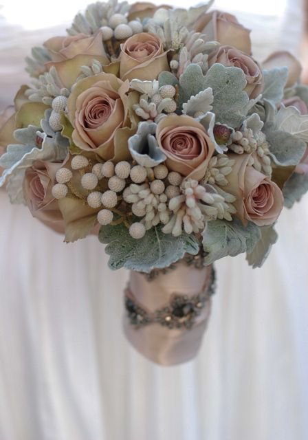 A bouquet of grey dusty miller leaves, grey kangaroo paws, silver brunia berry, and amnesia roses. The bouquet can be created throughout the year, but the silver brunia will come in and out of season. Photography by Vicki Grafton.