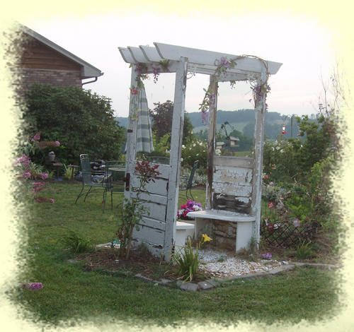 Garden Gazebo built from old doors, vintage headboard and reclaimed wood for inside bench. Old shutters are used to build flower boxes for the sides, and iron brackets enhance the looks of the front awning.