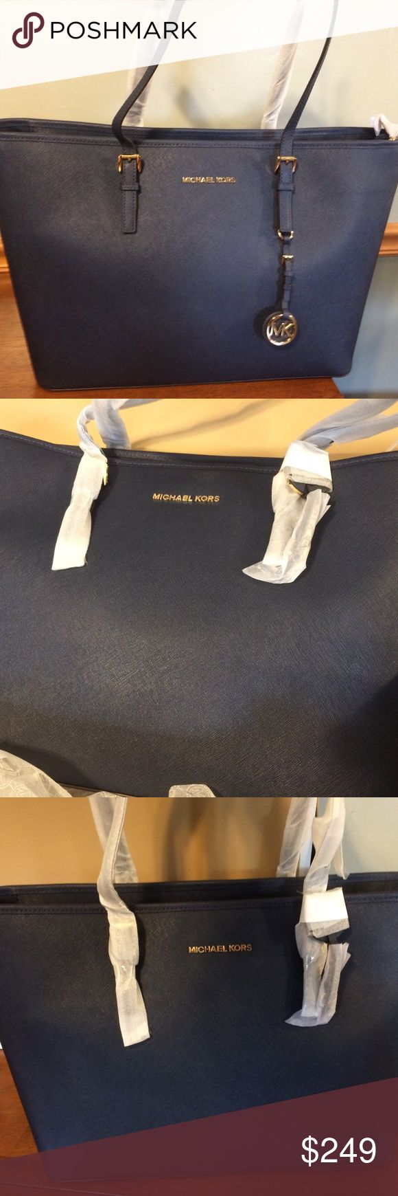 """NWT Michael Kors Jet Set Travel Medium Tote - Navy Jet Set Travel Medium Saffiano Leather Top-Zip Tote in hard to find Navy color. Beautiful, classic bag perfect for every day or travel use -- new with tags, still in tissue packaging.  Zip top with 3 large interior compartments, including a cushioned middle pocket perfect for laptop or tablet. 6 additional pockets (both open & zippered) to keep you organized throughout the day.  Dimensions: 11.5""""H x 15""""W x 5.5""""D; Handle Drop: 8.5"""" Michael…"""