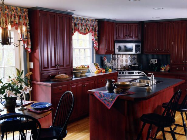 The tin back splash adds to country kitchen charm.  Love the farm red cabinets and blue counter tops.