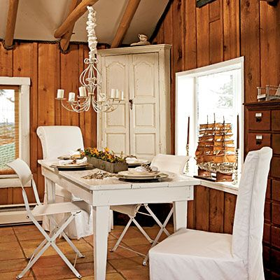 """Rustic Dining Room: Mexican tile floors give the dining room—which also doubles as an office—a more rustic look. """"The room had wood walls and wood beams, so I felt like that was enough,"""" homeowner Jerry West Sanders says. To connect the room with the rest of the interiors, she introduced touches of white in a painted table, corner cupboard, and chandelier."""