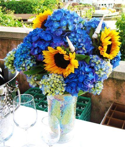 wine table arrangement  blue hydrangeas sunflowers and sea shells