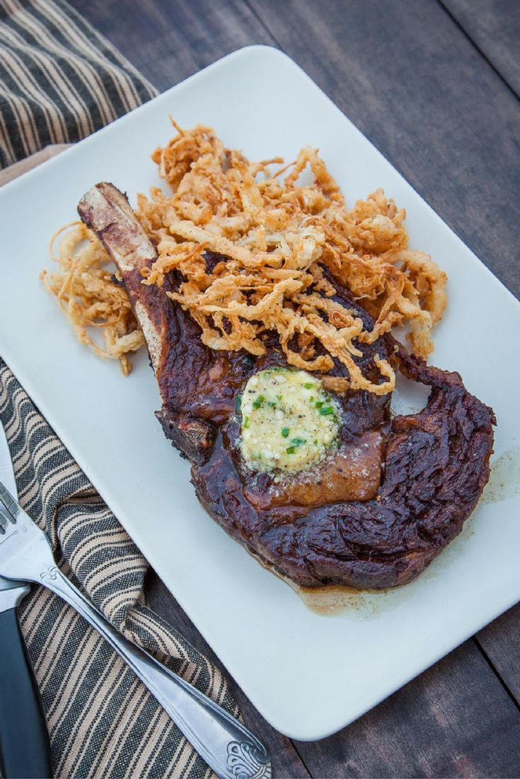 Cast Iron Skillet Seared Cowboy Steak with Gorgonzola Chives Compound Butter and Fried Onion Strings  Get the full recipe! http://steakbytes.com/recipes/cast-iron-skillet-seared-cowboy-steak-with-gorgonzola-chives-compound-butter-and-fried-onion-strings/
