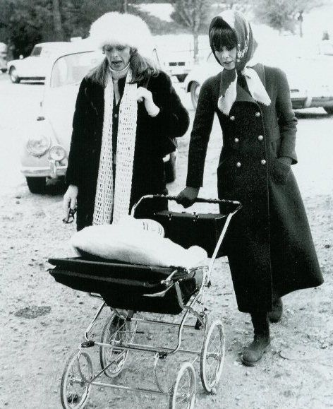 Capucine and her dear friend Mrs. Hepburn Dotti (with Luca in the pram) photographed in Rome, November 1970.    -Audrey was wearing a coat of Valentino and scarf of Givenchy.