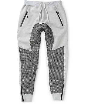 Add a unique jogger look to your collection with a black mesh leg and drop crotch overlay on a heather grey terry construction with two waterproof zipper hand pockets.