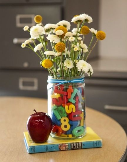 To make: find a big jar and a glass cup that fits inside. Carefully slide plastic alphabet letters (the kind that are magnets that stick to the fridge) between the jar and the glass cup. Fill the inside cup with water and flowers.