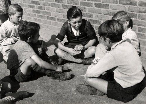 Jonge jongens zitten op straat te kaarten. Nederland, Sittard, 30 augustus 1950