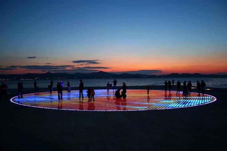 Zadar, era una de las vistas obligadas durante una ruta por Croacia.El Saludo al Sol, una muestra de arte moderno es obra de Nikola Bašić y sus ocho anillos de color representan los ocho planetas alrededor del sol. Un sol compuesto de 300 paneles fotovoltaicos formando un círculo de 22 m de diámetro