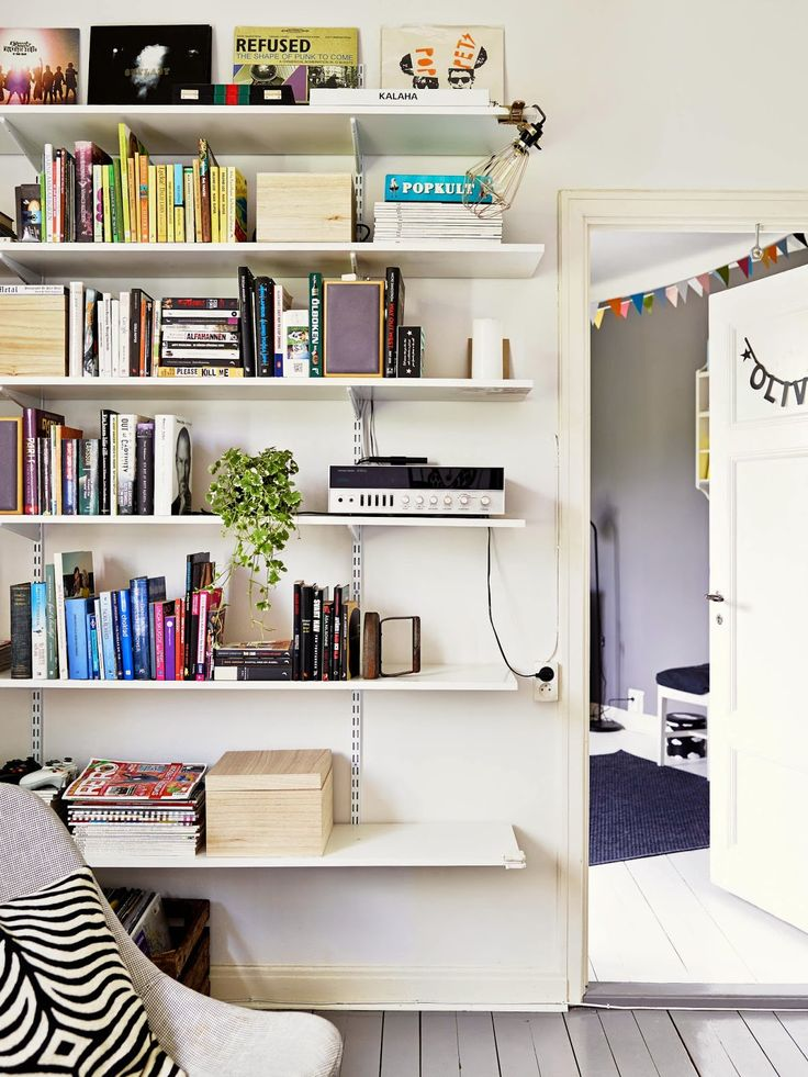 A grey and white Swedish home. Love the shelving and albums displayed.