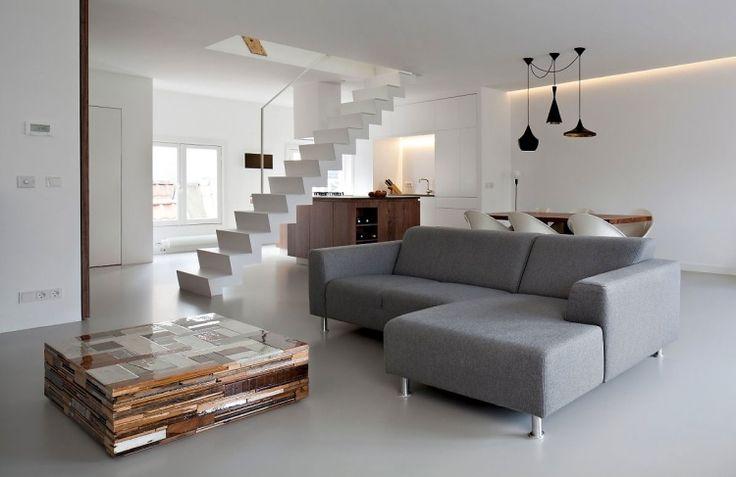 salon blanc avec un canapé gris, table basse cube en bois flotté et un escalier droit blanc