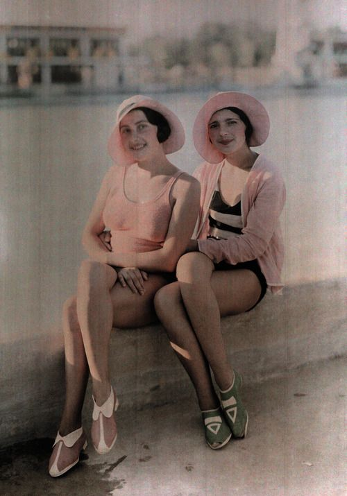 Two girls in bathing suits sit on a concrete ledge in Bucharest, Romania, November 1930.
