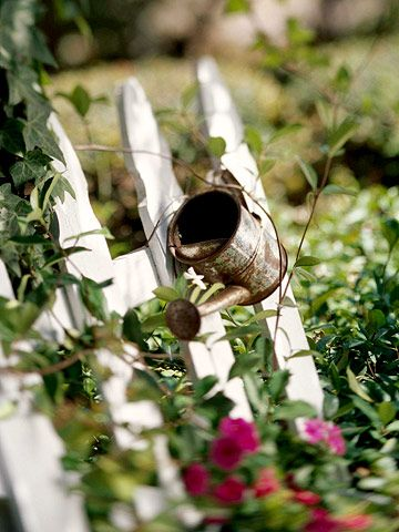 Add some little touches, like this well-worn watering can attached to the picket fence