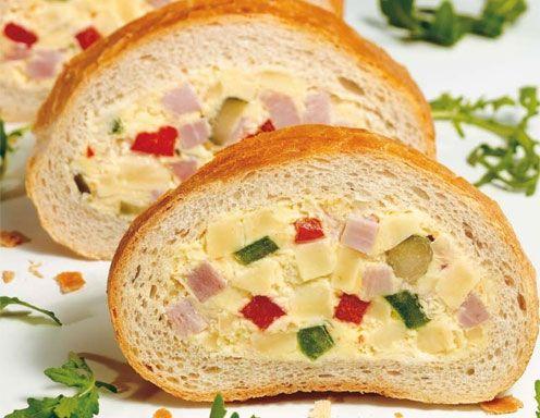 Für gefülltes Brot den halbierten Wecken höhlen Sie aus. Dann verrühren Sie mit einem Mixer Topfen, Teebutter, Crème fraîche und Gewürze. Wurst,