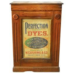 """Perfection Dye cabinet, wood w/paper litho on front door, mfgd by W. Cushing & Co.-Foxcraft, Maine, overall VG cond w/chip out of bottom front trim & ink stain on side, c.1890's, 24""""H x 17""""W x 6.5""""D."""