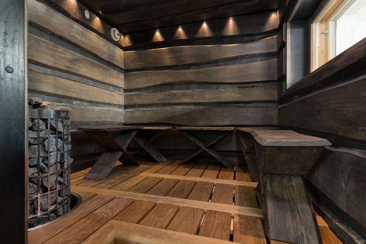 Tässä persoonallisessa saunassa on lauteiden tilalla penkit! Tyylikkäät, tummat lautaseinät ja kohdevalaistus ovat piste iin päälle. Lue myös:5 x upeimmat saunan lauteet