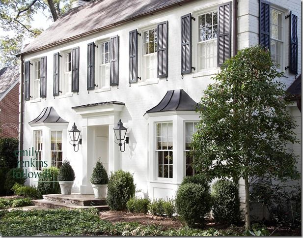 White brick colonial home with black shutters.