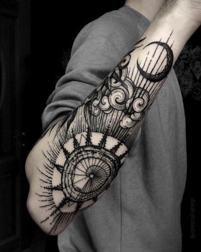 hier ist eine idee für einen schwarzen compass tattoo auf der hand eines manns   mit einem kompass, wolken und einem schwarzen mond