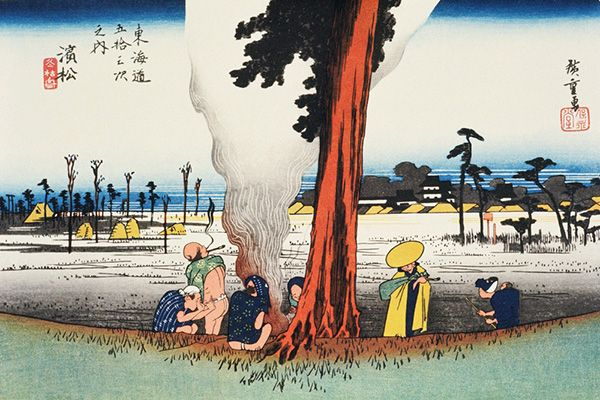Palanquin bearers and travellers warm themselves up by a campfire at the foot of a pine tree, surrounded by a desolate winter landscape on the outskirts of Hamamatsu. The seaside town was the 29th station on the Tokaido, centred around Hamamatsu Castle, which can be seen in the distance.