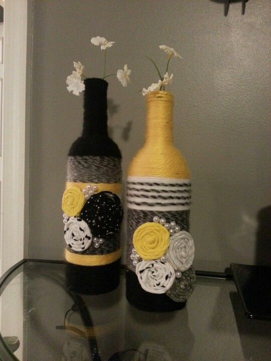 Yarn wrapped wine bottles with rolled fabric flowers and pearl accents.