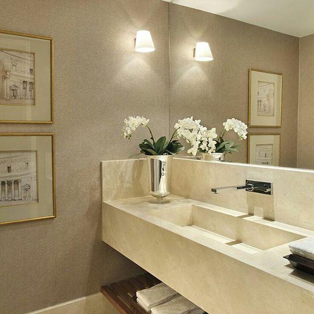 Banheiro com bancada em mármore esculpido, pintura com luminária e quadros com moldura dourada. Torneira cromada e gabinete/bancada em madeira ripada.