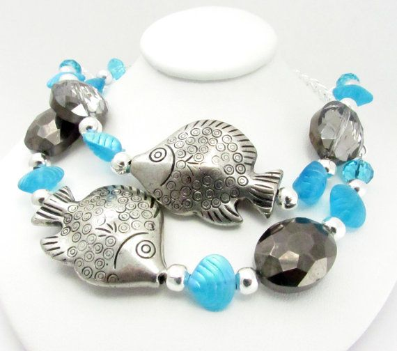 This set of 2 tropical fish curtain tiebacks are the perfect touch to add beach decor to your home. These tropical fish drapery holdbacks have beautiful shimmering sea shell charms and faceted crystal beads in a neutral color. These tropical seashell and fish curtain tiebacks measure 20 inches from end to end and have a 3/4 inch metal ring on ends for easy hanging.  This set of tropical curtain tie backs will look great in any home or beach home that has a tropical or nature inspired th...
