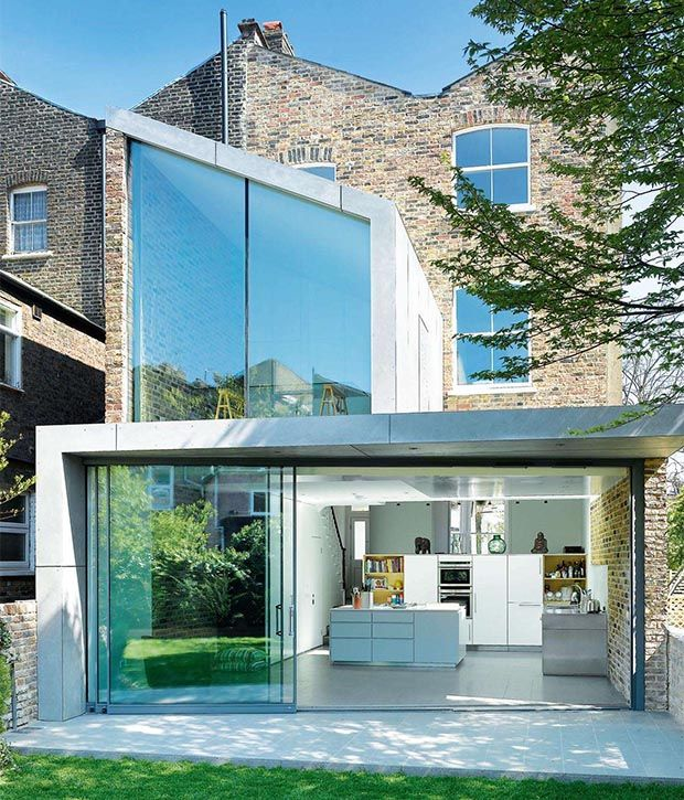 This Victorian end-of-terrace property has been given a striking new look thanks to the addition of a two-storey glazed extension. The ground floor now features a contemporary open-plan layout that is filled with natural light from the full-width glazing and large rooflights.