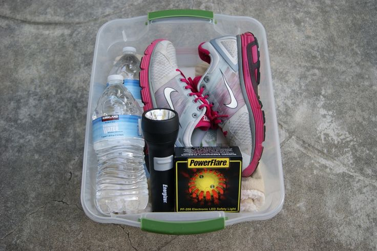 This is what my emergency kit for my car looks like, it has a blanket, an extra pair of sneakers and socks (just in case I am wearing heels or sandals and need to vacate my car and walk), a flashlight, a power flare, and water.