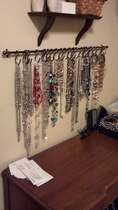 DIY necklace holder...small curtain rod and S-hooks, spray painted black and it would be perfect for hair ties/necklaces.
