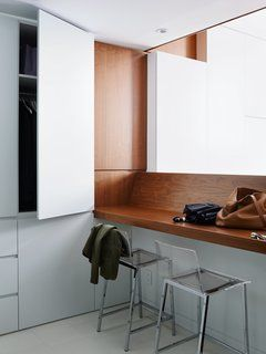 On the first level, a walnut veneer counter offers a place to drop belongings or to enjoy a meal. The walls are painted in Decorator's White by Benjamin Moore to create a bright but neutral backdrop. Maximizing space was the priority of the remodel.