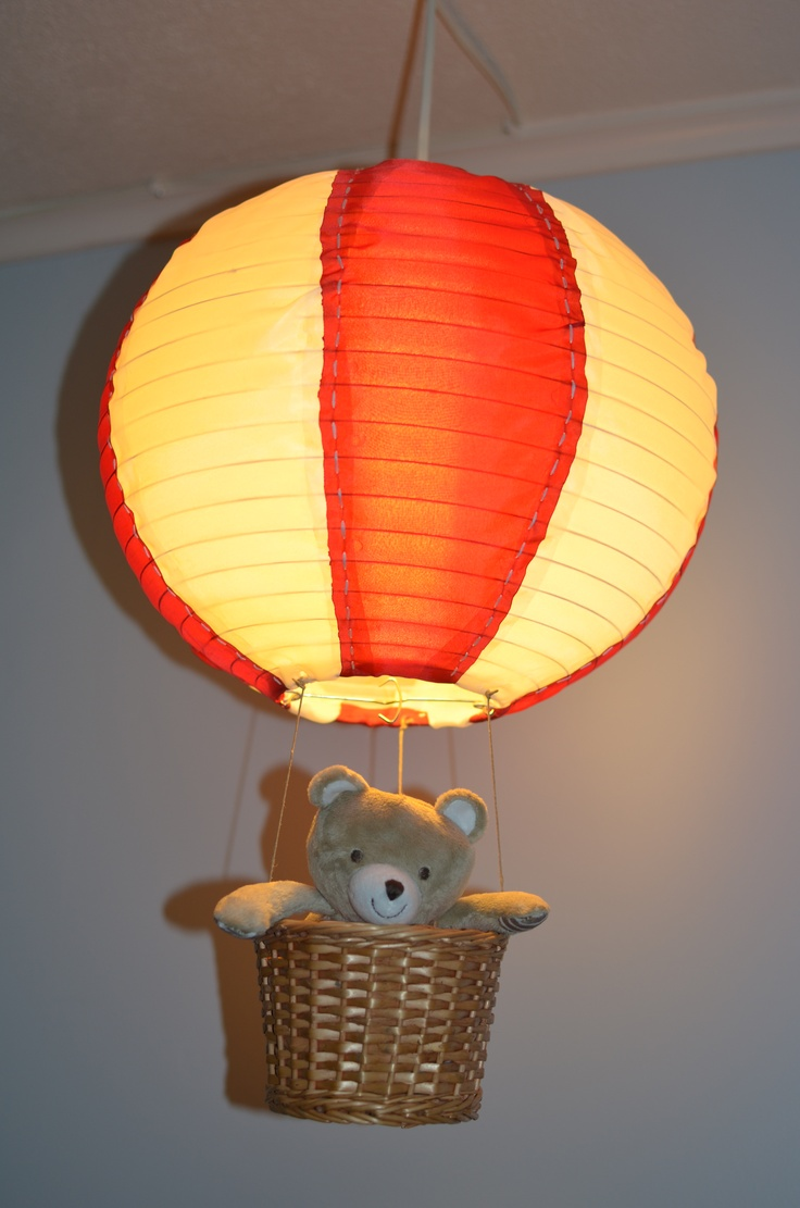 Hot air ballon lamp I made for my sons nursery. Matterials used: Light cord, paper lantern, nylon fabric, white embroidery floss, twine, a basket, hot glue and a lighter to burn edges of fabric so I would not have to hem them.