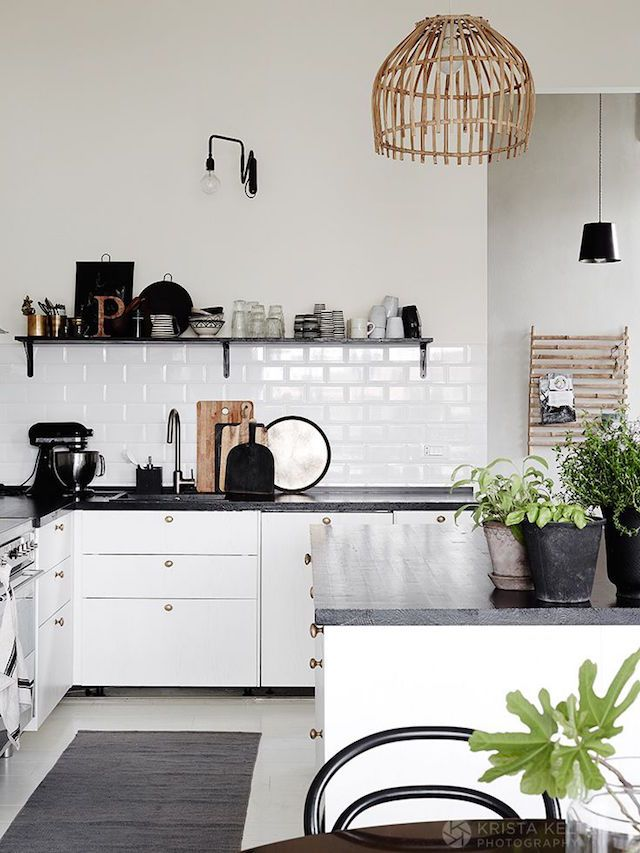 Scandinavian Style kitchen idea. White cabinets with black tabletop, open shelve, white tile and indoor plants.