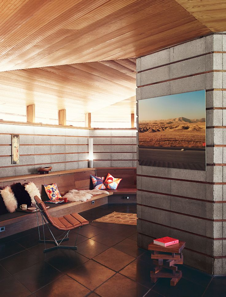 A Concrete Block Wall And A Built In Bench Line The Living Room,