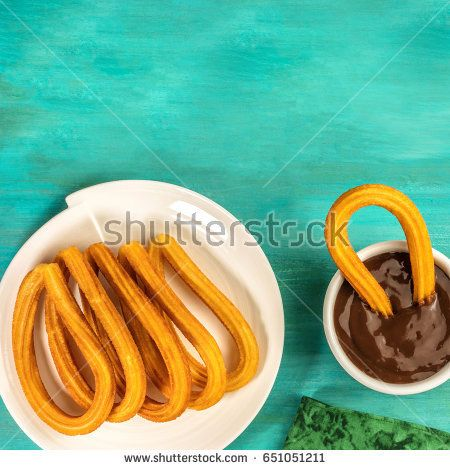 Plate of churros, traditional Spanish, especially Madrid, dessert, particularly for Sunday breakfast, with cup of hot chocolate, shot from above on turquoise table with copyspace, square photo