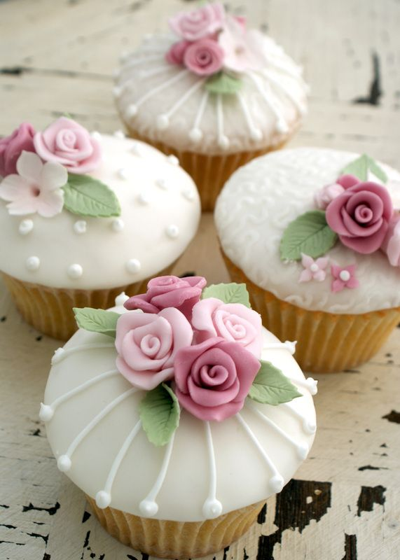Little birdcages, pearl dots and more with roses and mini flowers on fondant cupcakes