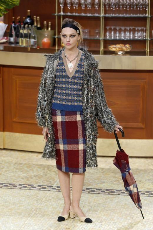 Das russische Model Sasha Pivovarova kommt kariert und hat einen Regenschirm dabei.