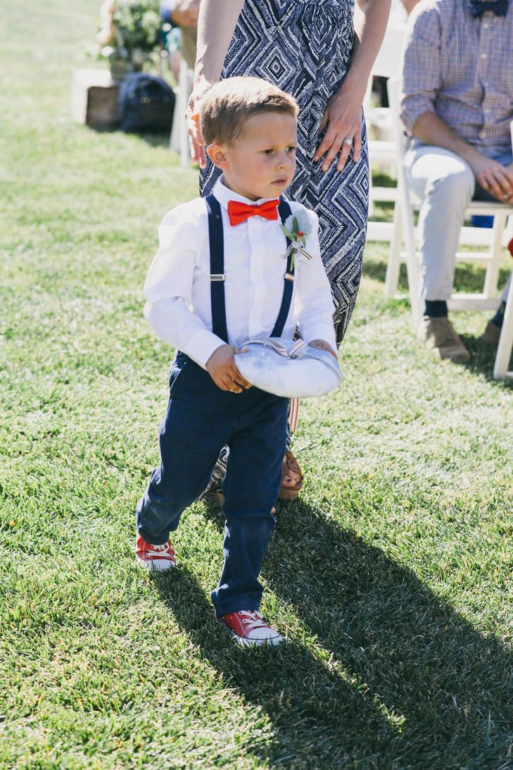 The ring bearer is dressed for a Fourth of July themed wedding wearing a red bow tie, navy slacks and suspenders, and red Converse sneakers