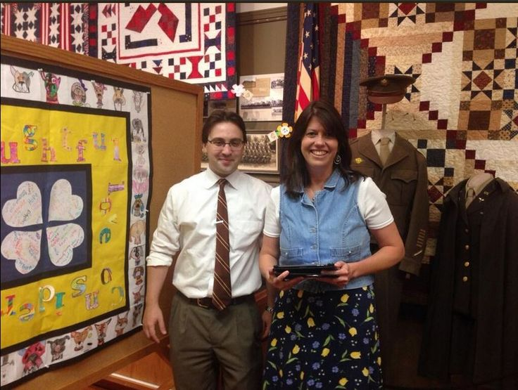 Ann Feldman, our tech guru on the quilt project, admires the paper version of the CritterKin Kindness Quilt with Sarpy Museum curator Ben Justman.