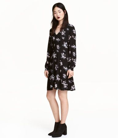 Black floral. V-neck dress in crinkled, woven viscose. Collar with ties at neckline, long sleeves with buttons at cuffs, concealed side zip, and seam at