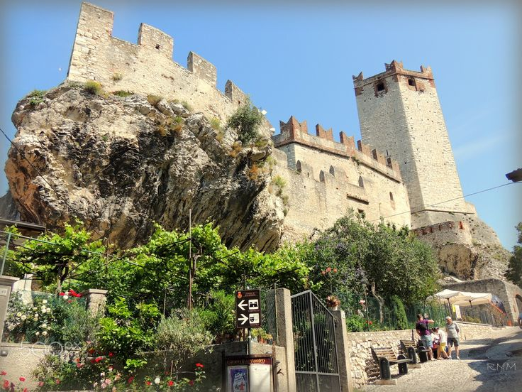The Castle on the rocks ............ - Castello Scaligero Malcesine's most prominent landmark is the Castello Scaligero, which has 13th-century fortifications and an older medieval tower in white natural stone. Like the castle of Sirmione at the southern end of the lake, it is named for the della Scala family of Verona who ruled the region in the 13th and 14th centuries, and has the characteristic swallow-tail Ghibelline merlon crenallations. Remnants of an Etruscan tomb have been found…