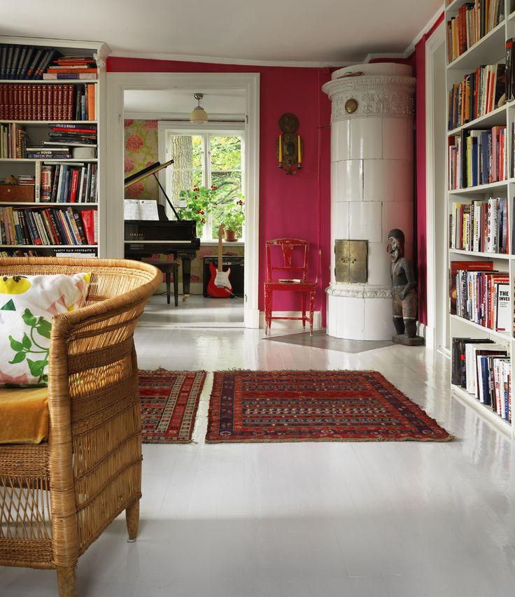 Vardagsrum med väggar målade i djuprosa och högblankt vitt trägolv. Vid kakelugnen står en afrikansk... #tile #stove #Swedish #fireplace #tile_stove #kakelugnen