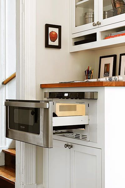 A microwave drawer fits neatly beneath a wood-countertop landing area for keys and mail. | Photo: Susan Teare