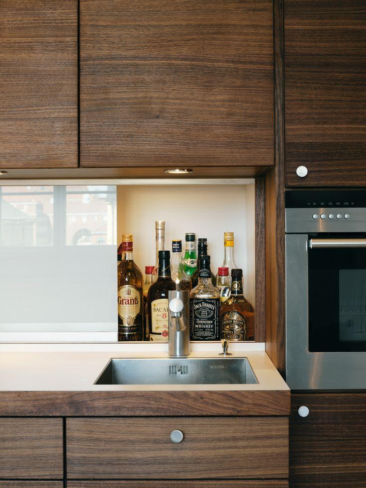 Walnut veneered cabinets, laminate counter top and bar behind sliding opaque glass panel/backsplass