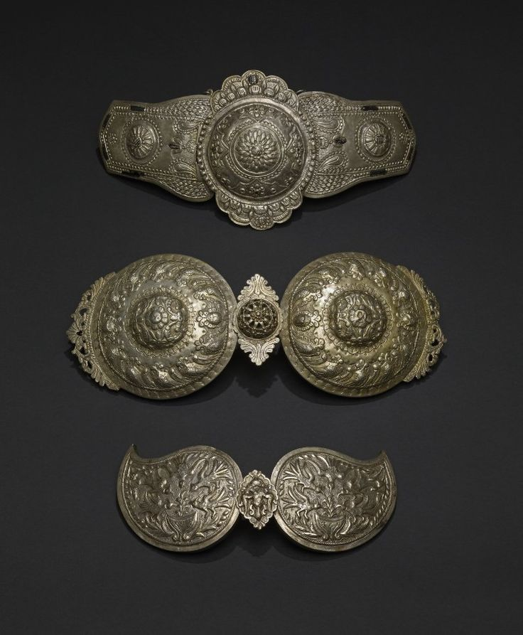 Belt clasp, copper alloy (?), formed of two oblong plates and a central disc with scalloped flange above and below, all with repoussé decoration of rosettes and foliate motifs, inlaid at intervals with a black composition, possibly paint. The clasp fastens with a hook beneath the central disc and a long chain which slots through a cylinder at the back to keep the two parts rigid.  Bugaria  19thC