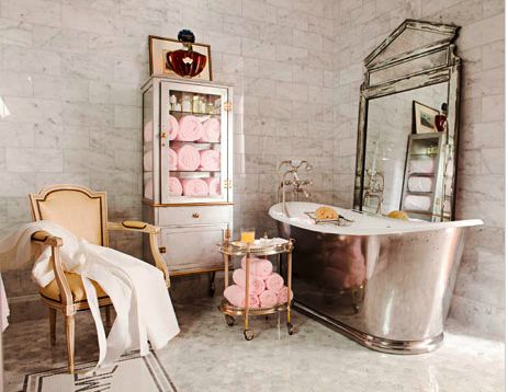 A Grand Parisian Hotel Inspired Guest Bathroom An Antique Chandelier Burnished Cast Iron Tub Silver Decor And Vintage Pharmacy Cabinet Give The