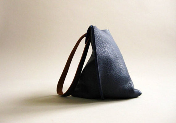 Available in two sizes, this sleek, unlined shoulder bag is crafted from thick, textured, supple indigo blue leather with medium length brown leather straps. The bag is finished with double screws and an interior keyring.  From Fog + Foundry. $165
