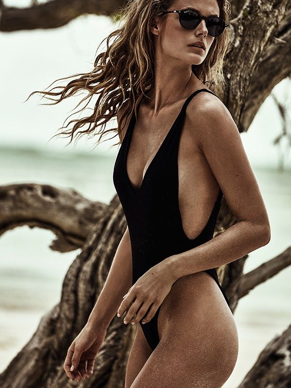 Kate Bock wears black one-piece swimsuit