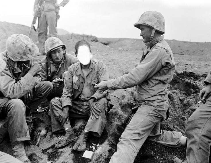 .S. Marines offer a Japanese prisoner of war, whose face is obliterated by censors, after he is captured during American invasion of Iwo Jima, Japanese Volcano Island stronghold, on Feb. 28, 1945 in World War II.  (AP Photo/Joe Rosenthal) #