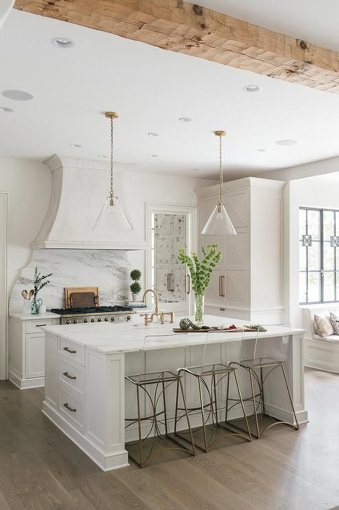 Two brass and glass conical light pendants illuminate a white center island fitted with a farmhouse